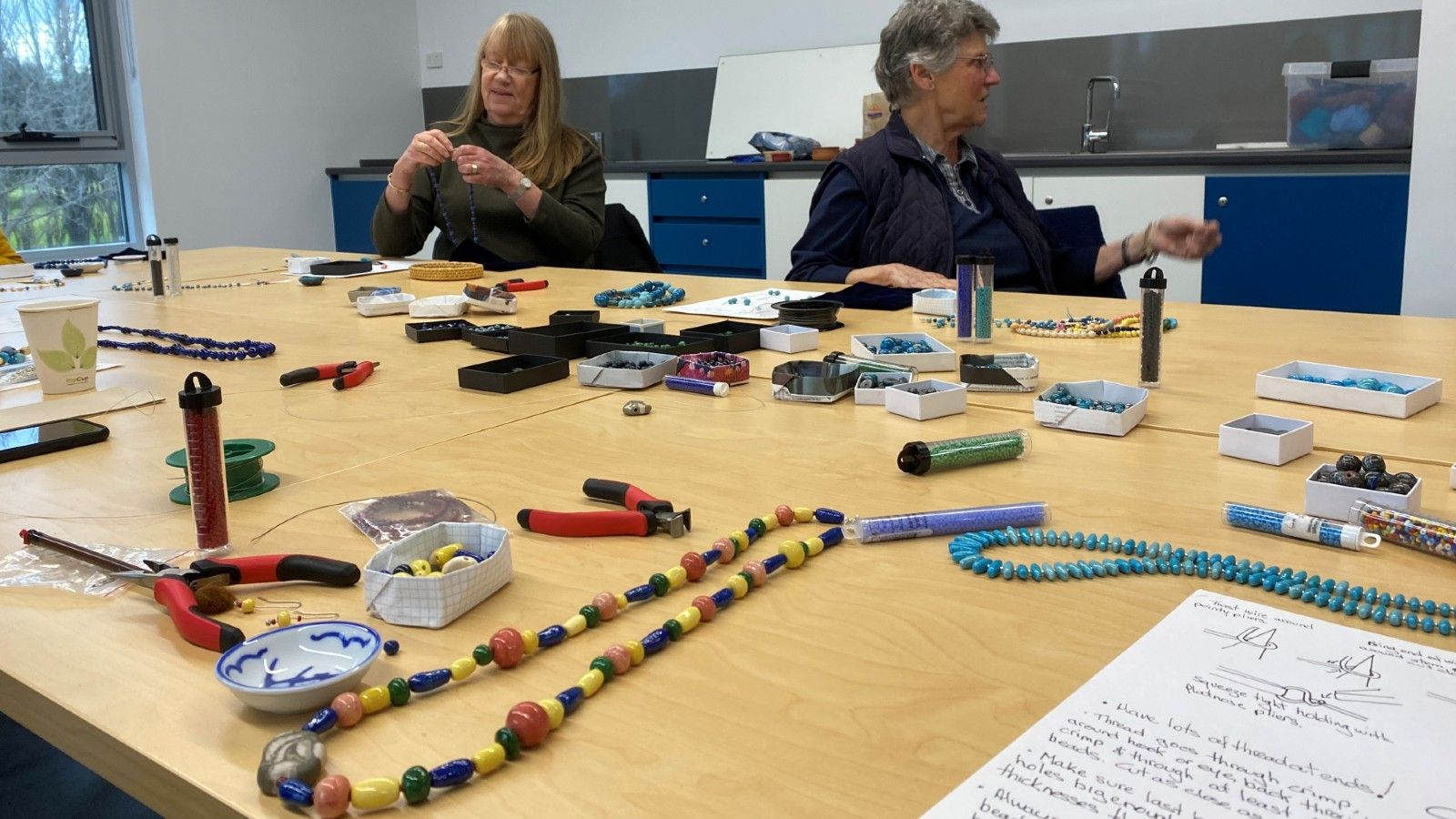 Photo of jewelry making tools and beads on a table.  banner image