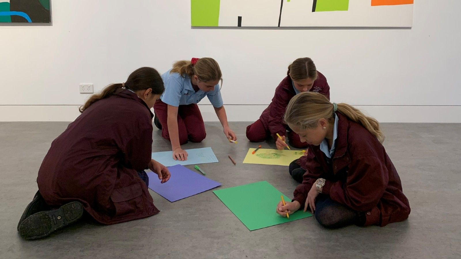 Photo of children sitting on the floor drawing. banner image